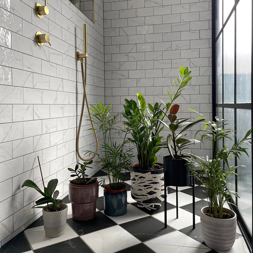marble checkerboard flooring and white marble wall tiles with various green plants and gold accessories