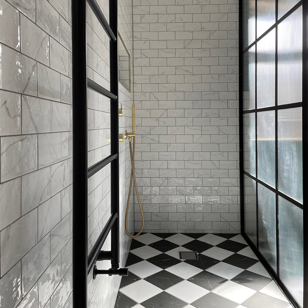 marble checkerboard flooring and white marble wall tiles with contemporary black accents and gold accessories