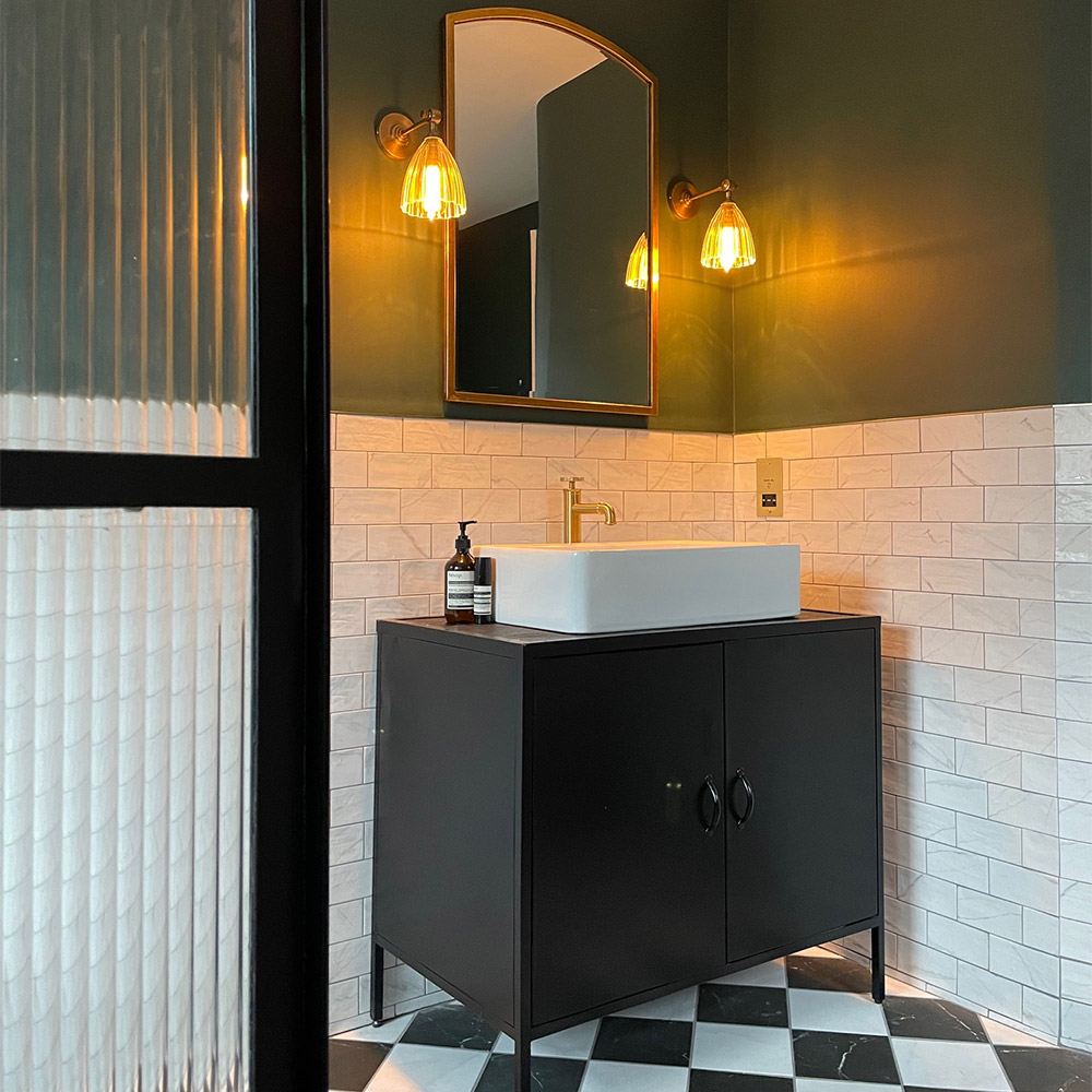 marble checkerboard flooring and white marble wall tiles with a green wall and gold accessories