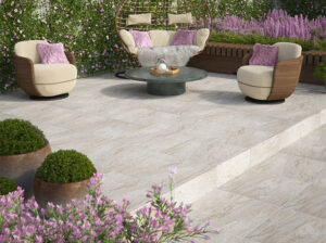 icaria beige tiles on a patio with purpe flowers and wicker chairs